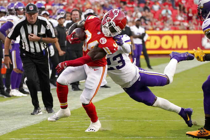 Kansas City Chiefs running back Darwin Thompson (34) runs with the ball as Minnesota Vikings safety Xavier Woods (23) defends during the first half of an NFL football game Friday, Aug. 27, 2021, in Kansas City, Mo. (AP Photo/Charlie Riedel)