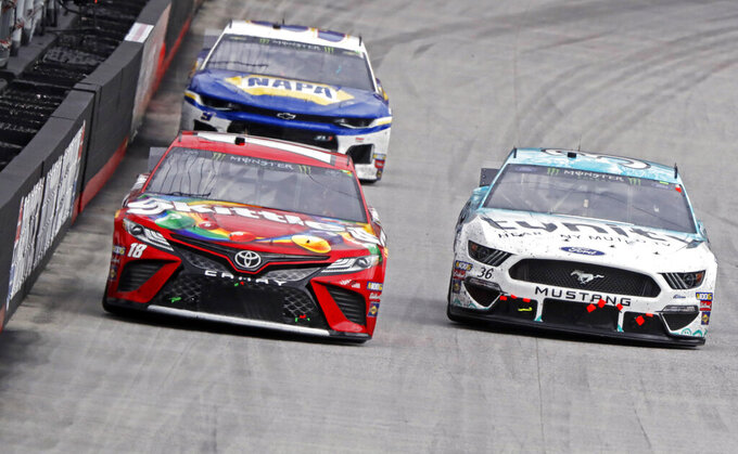 Kyle Busch (18) leads Matt Tifft (36) and Chase Elliott (9) down the back stretch during a NASCAR Cup Series auto race, Sunday, April 7, 2019, in Bristol, Tenn. (AP Photo/Wade Payne)