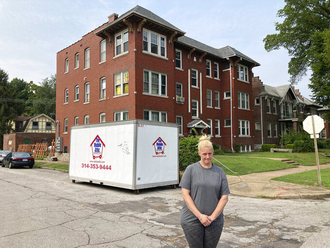 Kristen Bigogno stands in front of her St. Louis apartment on July 30, 2021. A storage trailer sits behind her. Bigogno expects to be evicted, along with her two teenage sons, soon after the federal moratorium ends after Saturday. She says they have no place to go and may face homelessness.(AP Photo by Jim Salter)