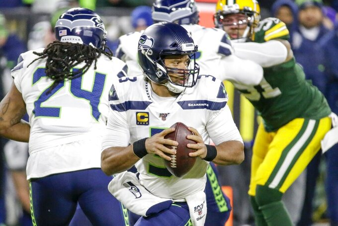 Seattle Seahawks quarterback Russell Wilson drops back during the first half of an NFL divisional playoff football game against the Green Bay Packers Sunday, Jan. 12, 2020, in Green Bay, Wis. (AP Photo/Mike Roemer)