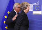 European Commission President Jean-Claude Juncker, left, pats British Prime Minister Theresa May on her back upon her arrival at EU headquarters in Brussels, Wednesday, Nov. 21, 2018. (AP Photo/Olivier Matthys)