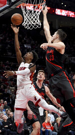 Miami Heat guard Josh Richardson, left, drives to the basket on Portland Trail Blazers center Jusuf Nurkic, right, during the first half of an NBA basketball game in Portland, Ore., Tuesday, Feb. 5, 2019. (AP Photo/Steve Dykes)