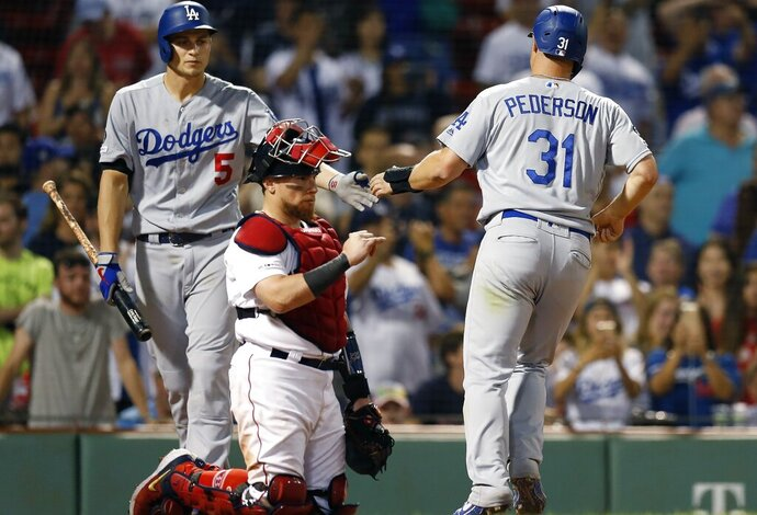 Los Angeles Dodgers' Joc Pederson (31) celebrates with Corey Seager (5) behind Boston Red Sox's Christian Vazquez after scoring on a bases-loaded walk during the 12th inning of a baseball game in Boston, Monday, July 15, 2019. (AP Photo/Michael Dwyer)