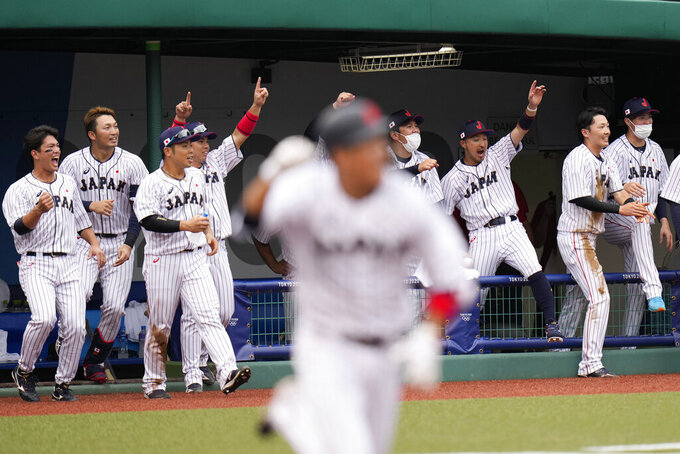 Japan players celebrate a walk-off single hit by Hayato Sakamoto, foreground, during the ninth inning of a baseball game against the Dominican Republic at the 2020 Summer Olympics, Wednesday, July 28, 2021, in Fukushima, Japan. Japan won 4-3. (AP Photo/Jae C. Hong)