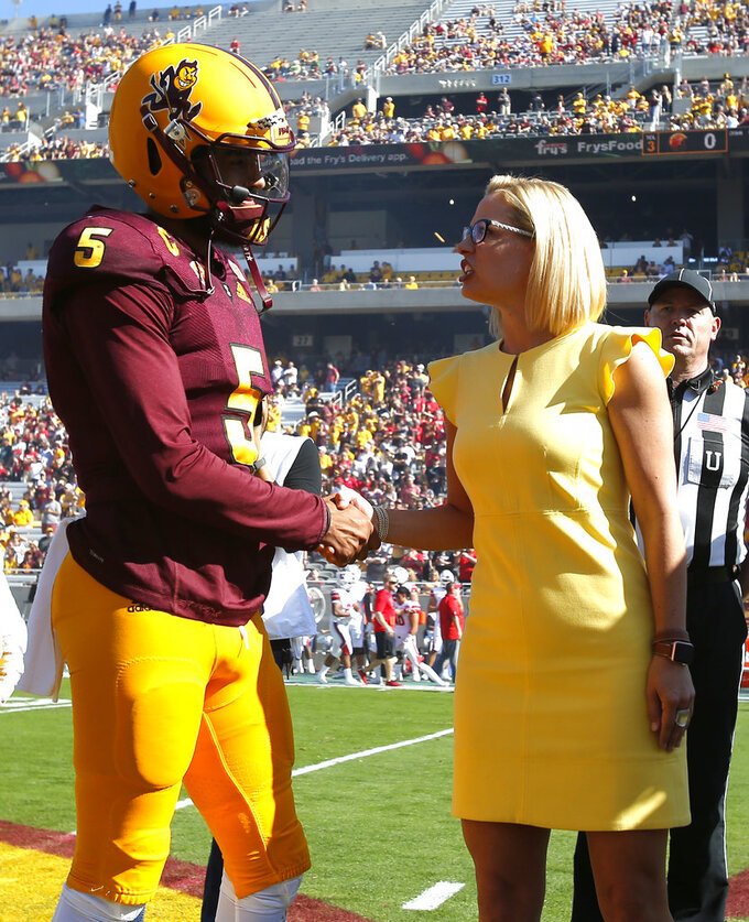 Democratic U.S. Senate candidate Kyrsten Sinema shakes hands with Arizona State's Kobe Williams during the coin toss before an NCAA college football game against Utah, Saturday, Nov 3, 2018, in Tempe, Ariz. (AP Photo/Rick Scuteri)