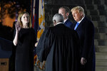 President Donald Trump watches as Supreme Court Justice Clarence Thomas administers the Constitutional Oath to Amy Coney Barrett on the South Lawn of the White House in Washington, Monday, Oct. 26, 2020, after Barrett was confirmed by the Senate earlier in the evening. Jesse Barrett holds the Bible. (AP Photo/Patrick Semansky)