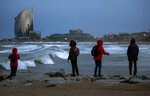Tourists look at the waves at the Mediterranean sea during strong winds in Barcelona, Spain, Sunday, Jan. 19, 2020. (AP Photo/Emilio Morenatti)