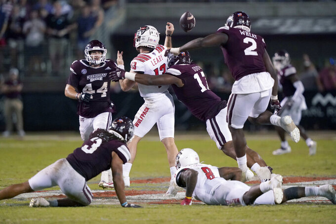 North Carolina State quarterback Devin Leary (13) is forced into fumbling by Mississippi State defensive end Aaron Odom (17) during the second half of an NCAA college football game in Starkville, Miss., Saturday, Sept. 11, 2021. (AP Photo/Rogelio V. Solis)