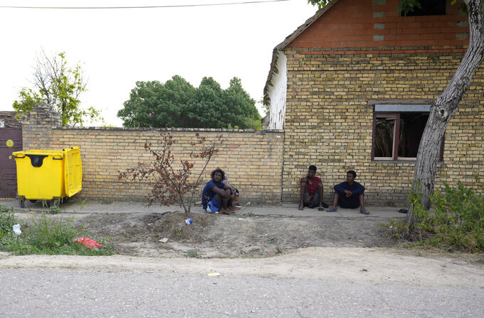 Migrants rest on a street in the village of Majdan, Serbia, Thursday, July 22, 2021. Empty or abandoned houses serve as temporary homes to people who fled their own homes in the Middle East, Africa or Asia with an aim to start a new life somewhere else. (AP Photo/Darko Vojinovic)