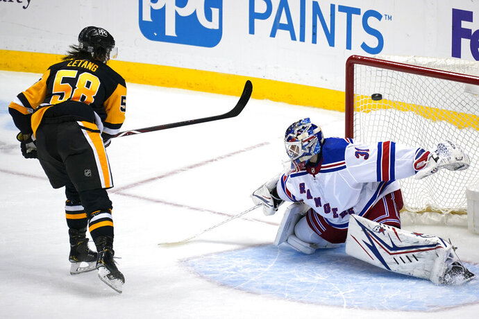 Pittsburgh Penguins' Kris Letang (58) lifts the puck over New York Rangers goaltender Igor Shesterkin for a shootout goal during an NHL hockey game in Pittsburgh, Friday, Jan. 22, 2021. (AP Photo/Gene J. Puskar)