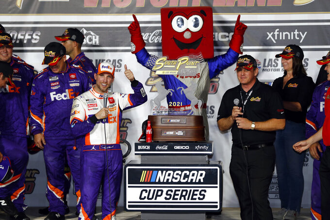NASCAR Cup Series driver Denny Hamlin, front left, celebrates with his trophy in Victory Lane after winning a NASCAR Cup Series auto race at the Las Vegas Motor Speedway, Sunday, Sept. 26, 2021, in Las Vegas. Ryan Growney, front right, general manager of the South Point hotel-casino, presented the trophy. (AP Photo/Steve Marcus)