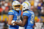 Los Angeles Chargers quarterback Justin Herbert, left, celebrates his touchdown throw to wide receiver Mike Williams (81) during the second half of an NFL football game against the Cleveland Browns Sunday, Oct. 10, 2021, in Inglewood, Calif. (AP Photo/Gregory Bull)