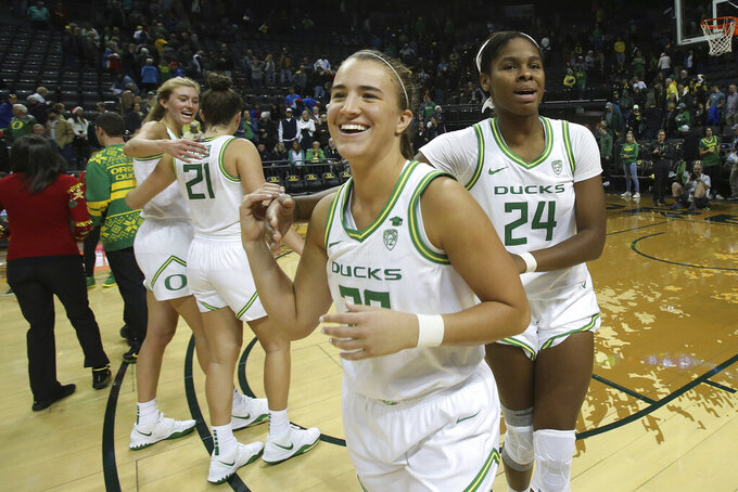 Oregon's Sabrina Ionescu, center, celebrates with her teammates Lydia Giomi, left, Erin Boley and Ruthy Hebard, right, after defeating Kansas State 89-51 in an NCAA college basketball game in Eugene, Ore., Saturday, Dec. 21, 2019. (AP Photo/Chris Pietsch)