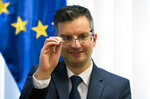Slovenia's prime minister Marjan Sarec inspects his glasses during an interview with the Associated Press in Ljubljana, Slovenia, Tuesday, April 23, 2019. (AP Photo/Darko Bandic)