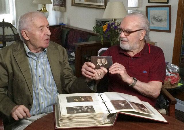 Brothers Alexander Feingold, left, and Joseph Feingold look at photo of themselves as boys in Joseph's apartment in New York on June 8, 2015. Joseph Feingold died at age 97 of complications from the new coronavirus, four weeks after his brother Alexander, 95, died of pneumonia at the same New York hospital. The brothers were Polish-born Holocaust survivors who had a difficult relationship shaped by the trauma of the war and the loss of their beloved mother and younger brother in Treblinka. The pandemic that gripped New York prevented a final farewell. (Raphaela Neihausen via AP)