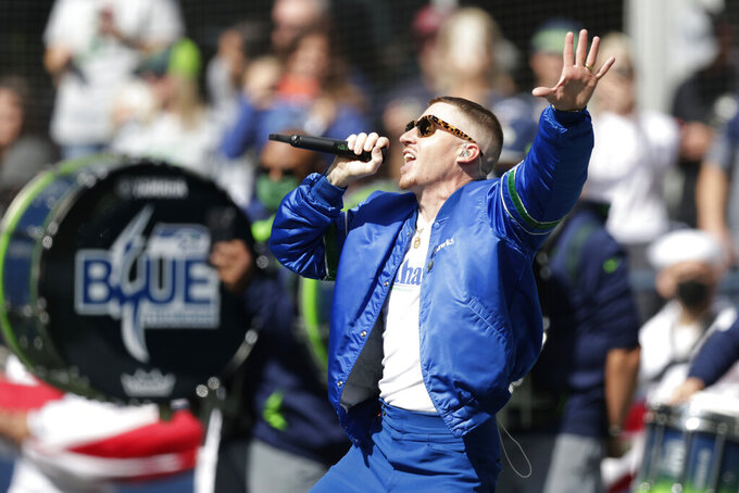 Rap singer Macklemore performs before an NFL football game between the Seattle Seahawks and the Tennessee Titans, Sunday, Sept. 19, 2021, in Seattle. (AP Photo/John Froschauer)