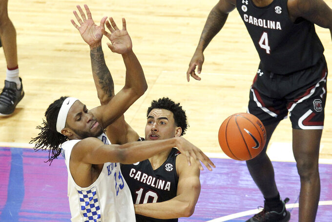 Kentucky's Isaiah Jackson, left, passes away from the defense of South Carolina's Justin Minaya (10) during the second half of an NCAA college basketball game in Lexington, Ky., Saturday, March 6, 2021. (AP Photo/James Crisp)