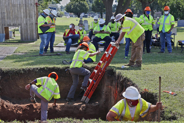 FILE - In this July 14, 2020, file photo, workers climb out of the excavation site as work continues on a potential unmarked mass grave from the 1921 Tulsa Race Massacre, at Oaklawn Cemetery in Tulsa, Okla. A second excavation begins Monday, Oct. 19, 2020, at a cemetery in an effort to find and identify victims of the 1921 Tulsa Race Massacre and shed light on violence that left hundreds dead and decimated an area that was once a cultural and economic mecca for African Americans. (AP Photo/Sue Ogrocki File)
