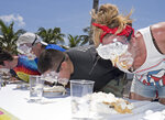 In this photo provided by the Florida Keys News Bureau, Steffany Stoeffler, right, competes with 24 other contestants at the Mile-High Key Lime Pie Eatin' Contest Thursday, July 4, 2019, in Key West, Fla. The competition, billed as a sweeter alternative to New York's July 4th hotdog-eating clash, kicked off Key West's Key Lime Festival that continues through Sunday, July 7. (Rob O'Neal/Florida Keys News Bureau via AP)