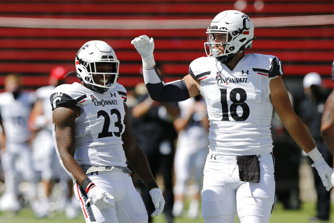 Cincinnati running back Gerrid Doaks, left, celebrates his touchdown with teammate Cam Jones against Austin Peay during the first half of an NCAA college football game Saturday, Sept. 19, 2020, in Cincinnati, Ohio. (AP Photo/Jay LaPrete)