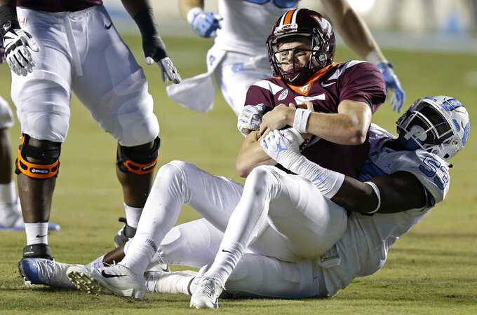 North Carolina's Malik Carney (53) tackles Virginia Tech quarterback Ryan Willis (5) during the first half of an NCAA college football game in Chapel Hill, N.C., Saturday, Oct. 13, 2018. (AP Photo/Gerry Broome)