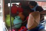 An Indian woman arranges plastic vessels filled with drinking water inside an autorickshaw at a water distribution point in Chennai, capital of the southern Indian state of Tamil Nadu, Wednesday, June 19, 2019. Millions of people are turning to water tank trucks in the state as house and hotel taps run dry in an acute water shortage caused by drying lakes and depleted groundwater. Some private companies have asked employees to work from home and several restaurants are closing early and even considering stopping lunch meals if the water scarcity aggravates. (AP Photo/R. Parthibhan)