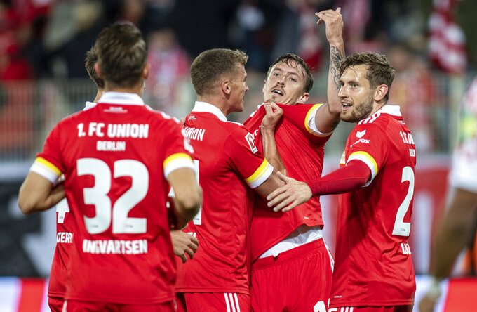 Union's Max Kruse, second right, reacts with teammates after scoring, during the German Bundesliga soccer match between FC Union Berlin and FSV Mainz, at the Stadion An der Alten Forsterei, in Berlin, Friday, Oct. 2, 2020. (Andreas Gora/dpa via AP)