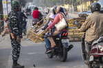 An Indian family rides past police barricades damaged by protestors in Gauhati, India, Thursday, Dec. 12, 2019. Police arrested dozens of people and enforced curfew on Thursday in several districts in India's northeastern Assam state where thousands protested legislation granting citizenship to non-Muslims who migrated from neighboring countries. (AP Photo/Anupam Nath)