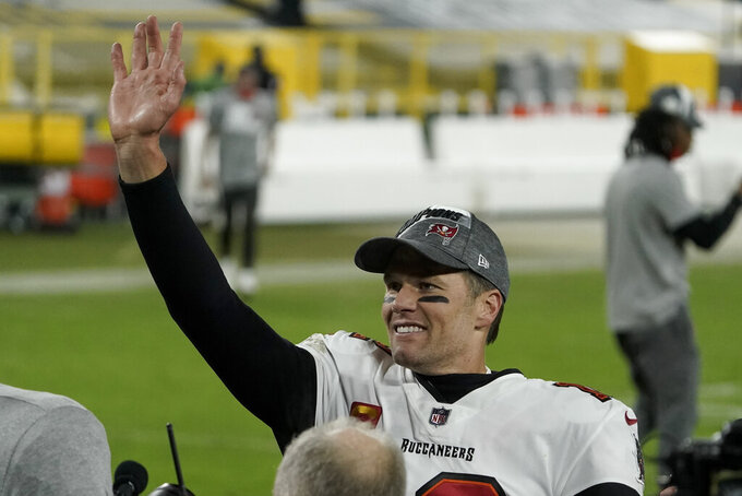 Tampa Bay Buccaneers quarterback Tom Brady waves to spectators after winning the NFC championship NFL football game against the Green Bay Packers in Green Bay, Wis., Sunday, Jan. 24, 2021. The Buccaneers defeated the Packers 31-26 to advance to the Super Bowl. (AP Photo/Morry Gash)
