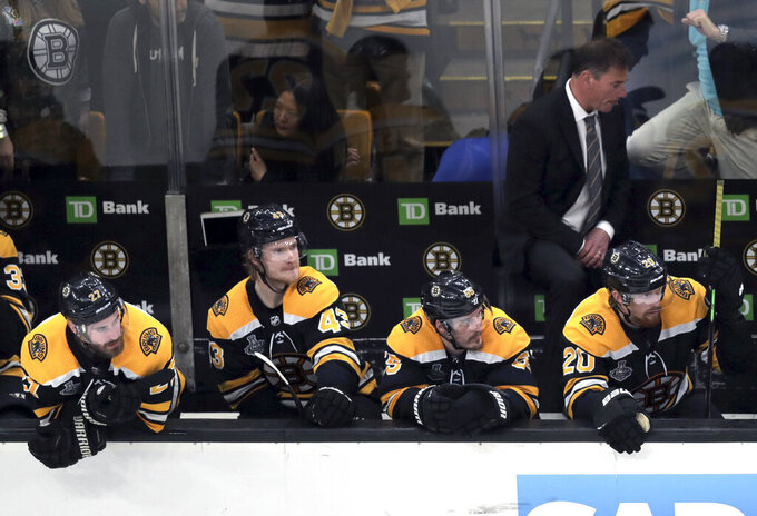 Boston Bruins players and head coach Bruce Cassidy, right rear, watch the final minutes in Game 5 of the NHL hockey Stanley Cup Final against the St. Louis Blues, Thursday, June 6, 2019, in Boston. (AP Photo/Charles Krupa)