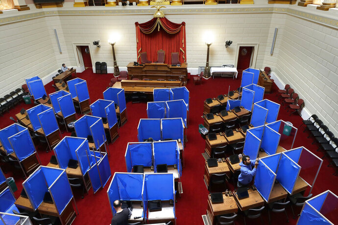 Workers install plastic partitions, with a blue removable protective covering, between desks, Monday, June 15, 2020, on the floor of the House Chamber at the Statehouse, in Providence, R.I. The partitions are being installed before the expected return of lawmakers to the Statehouse on Wednesday, June 17. (AP Photo/Steven Senne)
