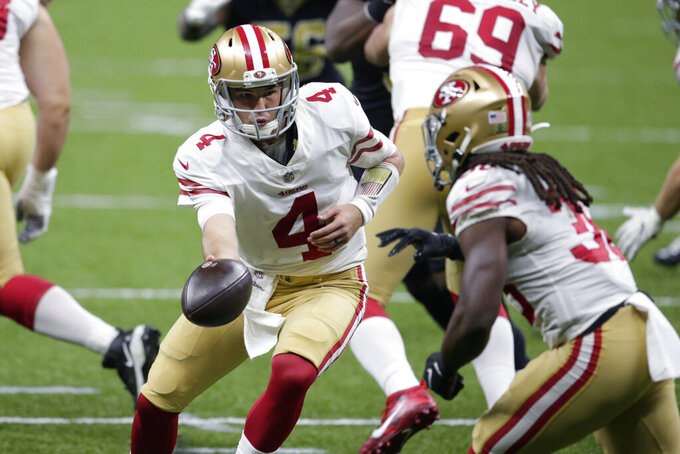 San Francisco 49ers quarterback Nick Mullens (4) hands off to running back JaMycal Hasty in the first half of an NFL football game against the New Orleans Saints in New Orleans, Sunday, Nov. 15, 2020. (AP Photo/Butch Dill)