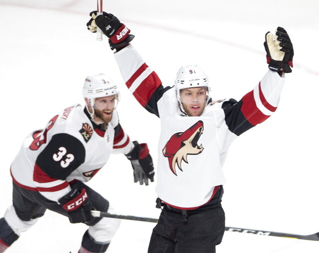 Arizona Coyotes left wing Taylor Hall (91) celebrates with teammate Alex Goligoski (33) after scoring the second goal against the Montreal Canadiens during second period NHL hockey action, Monday, Feb. 10, 2020 in Montreal. (Ryan Remiorz/The Canadian Press via AP)