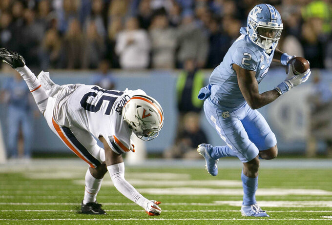 North Carolina's Dyami Brown (2) breaks away from Virginia's De'Vante Cross (15) on a 47-yard pass completion from quarterback Sam Howell for a touchdown during the second quarter of an NCAA college football game Saturday, Nov. 2, 2019, in Chapel Hill, N.C. (Robert Willett/The News & Observer via AP)