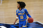 UCLA guard Tyger Campbell drives up court during the first half of an Elite 8 game against Michigan in the NCAA men's college basketball tournament at Lucas Oil Stadium, Tuesday, March 30, 2021, in Indianapolis. (AP Photo/Michael Conroy)