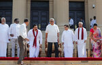 Sri Lankan president Gotabaya Rajapaksa prepares to sit for photographs with his new cabinet members in Colombo, Sri Lanka, Friday, Nov. 22, 2019. Rajapaksa, who was elected last week, said he would call a parliamentary election as early as allowed. The parliamentary term ends next August, and the constitution allows the president to dissolve Parliament in March and go for an election. (AP Photo/Eranga Jayawardena)