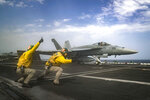 In this Thursday, May 16, 2019 photo released by the U.S. Navy, Lt. Nicholas Miller, from Spring, Texas, and Lt. Sean Ryan, from Gautier, Miss., launch an F-18 Super Hornet from the deck of the USS Abraham Lincoln aircraft carrier in the Arabian Sea. On Saturday, May 18, 2019, U.S. diplomats warned that commercial airliners flying over the wider Persian Gulf faced a risk of being