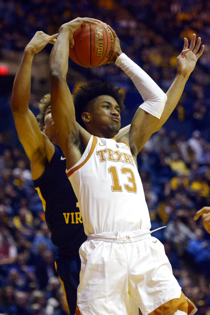 FILE - In this Feb. 9, 2019, file photo, Texas guard Jase Febres (13) catches a rebound during the second half of an NCAA college basketball game against West Virginia in Morgantown, W.Va. Texas led the Big 12 with 325 3-pointers. But at a rate of 34.8 percent, their make-to-miss ratio was about average nationally. Febres made a team-high 89 shots from long range last season. (AP Photo/Craig Hudson, File)