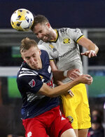 New England Revolution forward Adam Buksa (9) and Columbus Crew defender Josh Williams (3) view for a header during the first half of a MLS soccer match, Saturday, Sept. 18, 2021, in Foxborough, Mass. (AP Photo/Mary Schwalm)