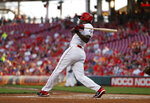 Cincinnati Reds' Aristides Aquino follows through on an RBI single off Philadelphia Phillies starting pitcher Vince Velasquez during the first inning of a baseball game Tuesday, Sept. 3, 2019, in Cincinnati. (AP Photo/Gary Landers)