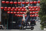 FILE - In this July 11, 2020, file photo, a woman wears a face mask while riding a scooter in front lanterns hanging in Chinatown during the coronavirus outbreak in San Francisco. In San Francisco, a city that depends largely on tourism, a nearly $11 billion loss in tourism spending is projected in 2020 and 2021 as the thousands of people who normally flock their for conventions and vacations have disappeared, according to the city's tourism bureau. (AP Photo/Jeff Chiu, File)