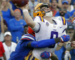 FILE - In this Oct. 6, 2018, file photo, Florida defensive lineman Jachai Polite, left, hits LSU quarterback Joe Burrow just as he releases a pass during the second half of an NCAA college football game in Gainesville, Fla. Polite, a junior defensive end, has seven sacks in as many games and at least one in each of the last five. (AP Photo/John Raoux, File)