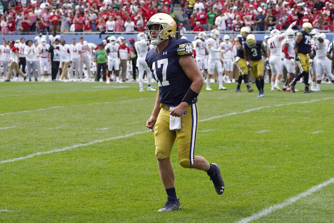 Notre Dame quarterback Jack Coan limps off the field injured during the second half of an NCAA college football game against Wisconsin Saturday, Sept. 25, 2021, in Chicago. Coan did not return to play. (AP Photo/Charles Rex Arbogast)