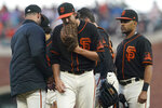 San Francisco Giants' Kevin Gausman, middle, walks off the mound after being taken out for a relief pitcher by manager Gabe Kapler, left, during the fifth inning of the team's baseball game against the Pittsburgh Pirates in San Francisco, Saturday, July 24, 2021. (AP Photo/Jeff Chiu)