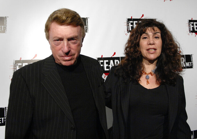 File-This Oct. 30, 2006, file photo shows writer, director Larry Cohen, left, and wife Cynthia Cohen arriving for the Comcast, Sony and Lionsgate launch party for FEARnet, a multi-platform network dedicated to horror, held at the Boulevard 3 nightclub in Los Angeles.  Cohen, the maverick B-movie director of cult horror films