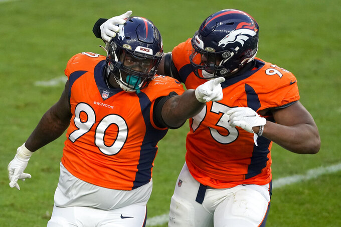 Denver Broncos defensive end DeShawn Williams (90) celebrates his sack against the Miami Dolphins with defensive end Dre'Mont Jones (93) during the second half of an NFL football game, Sunday, Nov. 22, 2020, in Denver. (AP Photo/Jack Dempsey)