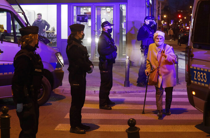 A woman crosses a street as police surround a bar they raid in Warsaw, Poland, Friday March 26, 2021. A raft of new pandemic restrictions take effect in Poland on Saturday to slow the spread of infection in what has become of the new global hot spot for the virus, but even earlier restrictions are being defied by some.(AP Photo/Czarek Sokolowski)