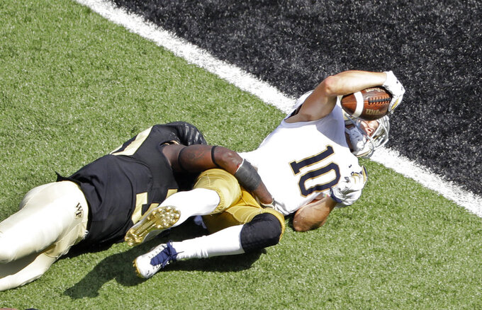 Notre Dame's Chris Finke (10) tries to reach the ball over the goal line as he is stopped by Wake Forest's Ja'Cquez Williams (30) in the second half of an NCAA college football game in Winston-Salem, N.C., Saturday, Sept. 22, 2018. (AP Photo/Chuck Burton)