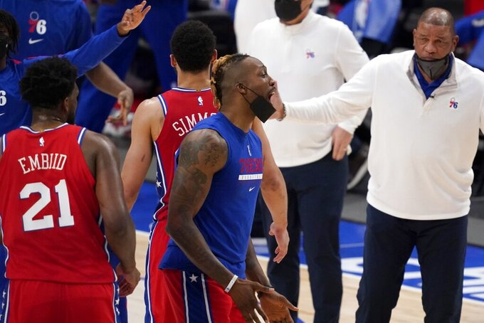 Philadelphia 76ers' Joel Embiid (21), Dwight Howard, center and head coach Doc Rivers, right, celebrate during a time out in the second half of an NBA basketball game against the Dallas Mavericks in Dallas, Monday, April 12, 2021. The 76ers won 113-95. (AP Photo/Tony Gutierrez)