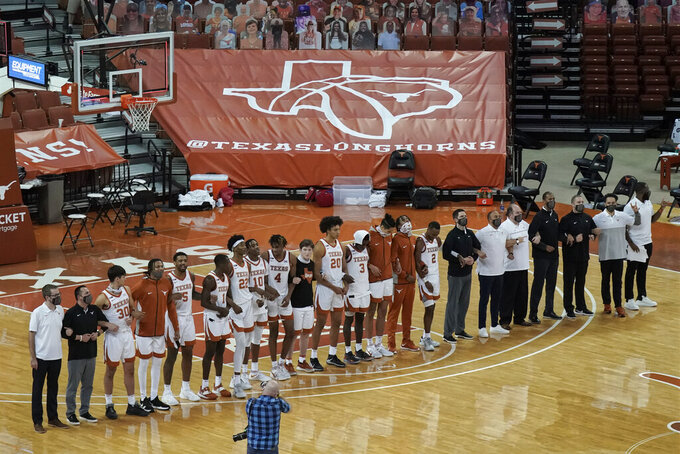 """FILE - In this Sunday, Dec. 20, 2020, file photo, Texas players sing """"The Eyes Of Texas"""" after an NCAA college basketball game against Oklahoma State in Austin, Texas. The University of Texas' long-awaited report on the history of the school song """"The Eyes of Texas"""" found it had """"no racist intent,"""" but the school will not require athletes and band members to participate in singing or playing it at games and campus events. The song had erupted in controversy in 2020 after some members of the football team demanded the school stop playing it because of racist elements in the song's past. (AP Photo/Chuck Burton, File)"""